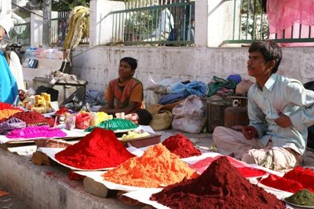 Gekleurd poeder voor het aanstaande Holi-feest is ook te koop op de markt