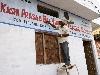 Schilder Ashok schildert de schoolnaam op de nieuwe gevel van de school